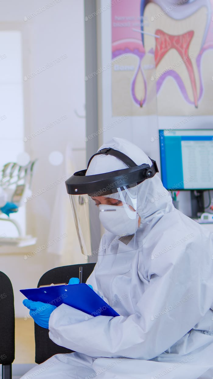 Dentist with face shield talking with elderly woman before examination