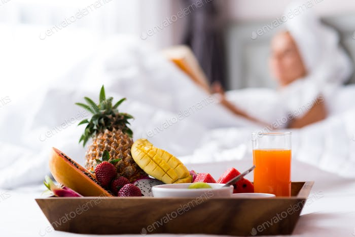 Close up of a tray with fruits in bed