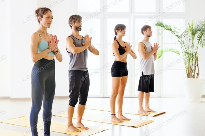 Small group of people practicing yoga in studio