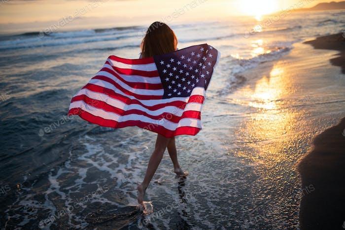 Glückliche Frau, die am Strand läuft, während der Unabhängigkeitstag feiert und Freiheit in den USA genießen