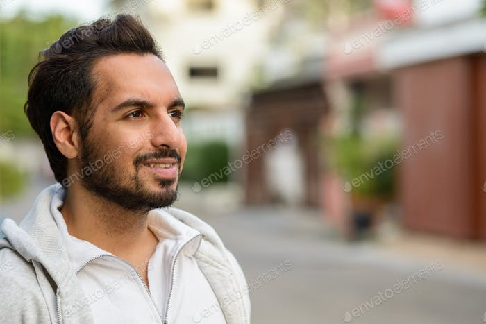 Portrait of young happy Indian man thinking outdoors