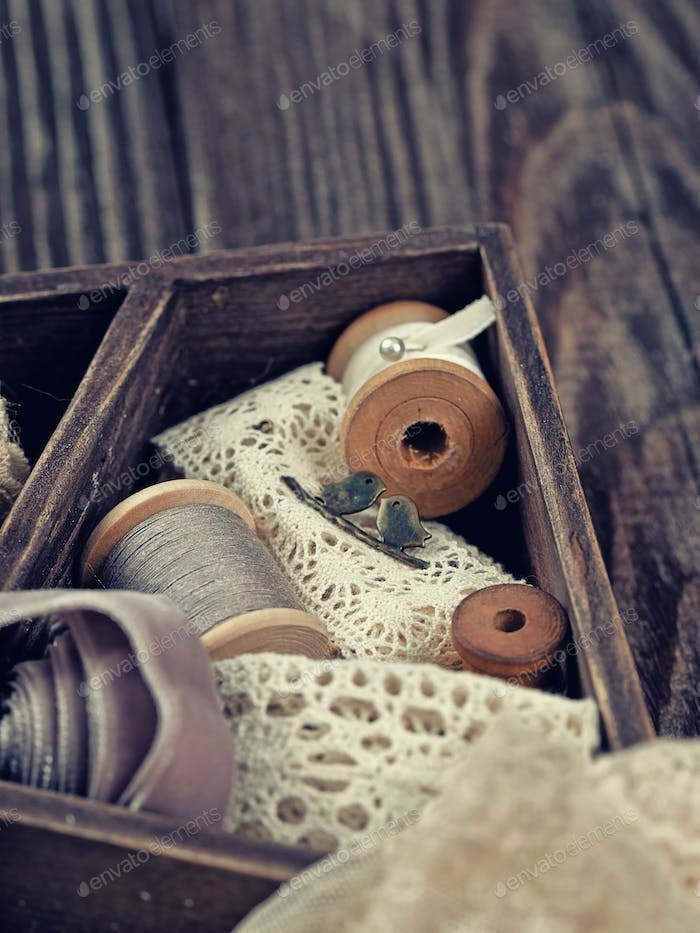 Wooden box with laces, ribbons and threads