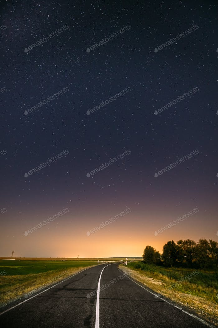 Night Starry Sky Above Country Road In Countryside And Green Fie