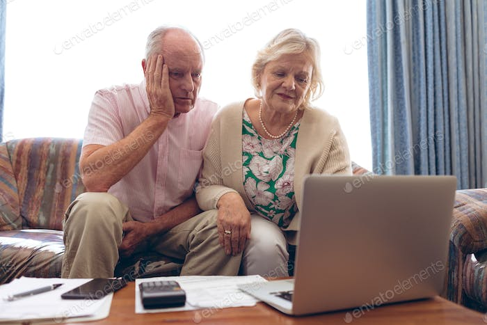 Front view of senior Caucasian couple looking medical report on laptop at retirement home