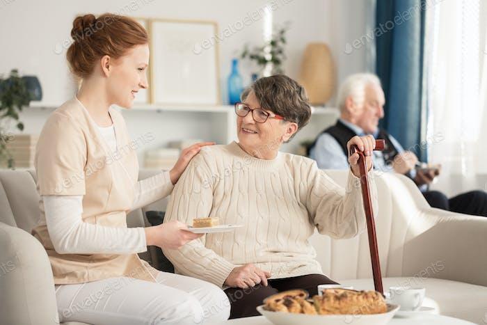 Nurse serving cake for pensioner
