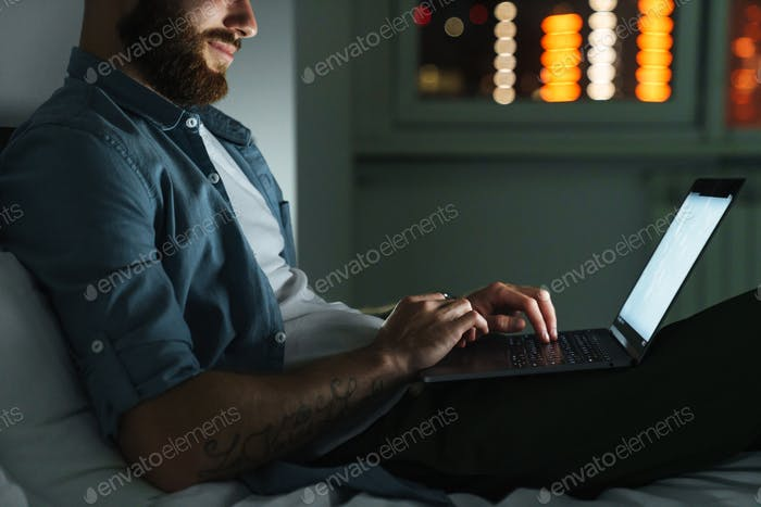 young bearded man laying on bed at home at night