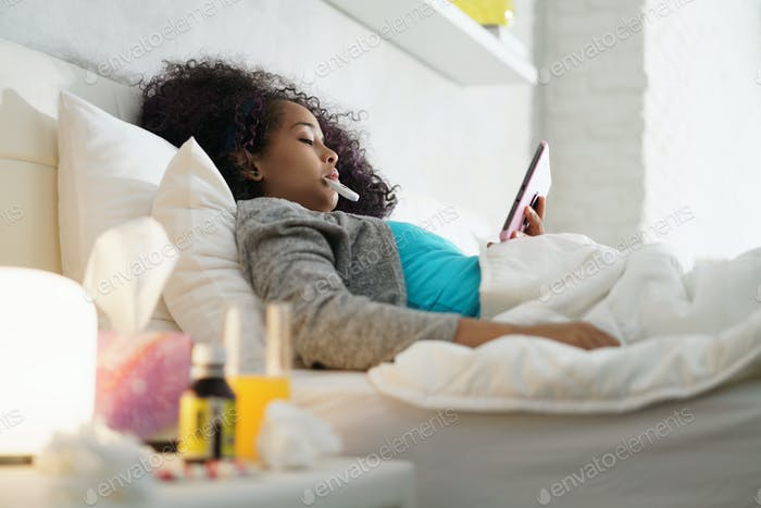 Girl With Fever Using Thermometer And Tablet In Bed