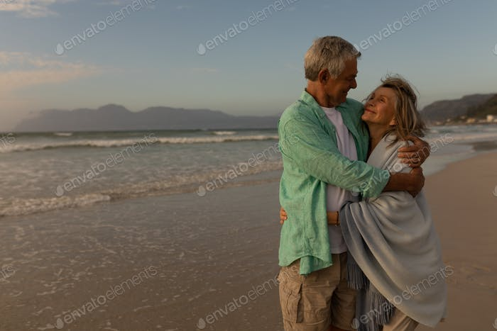 Active senior couple embracing each other on the beach
