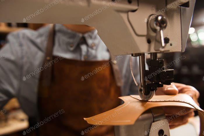 Close up of a cobbler using sewing machine