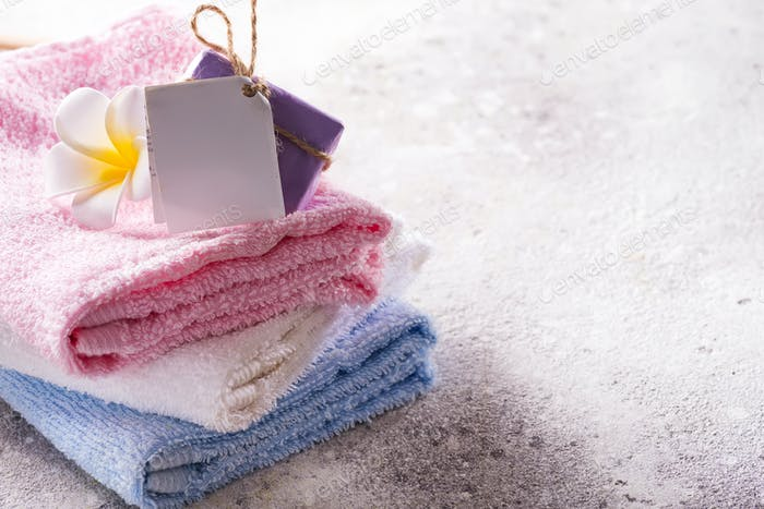 Lots of colorful bath towels stacked on each other with hand soap and flower on light stone