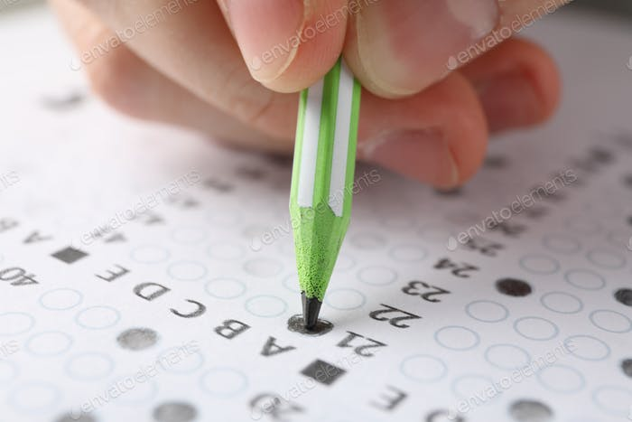 Student fills answers test sheet, close up