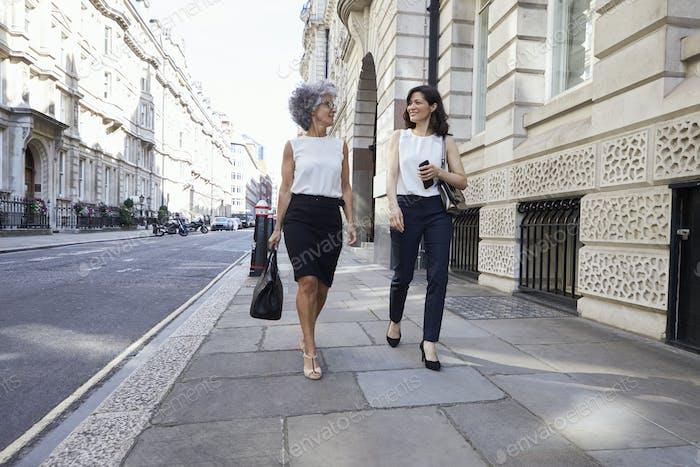 Two female colleagues walking in the street talking