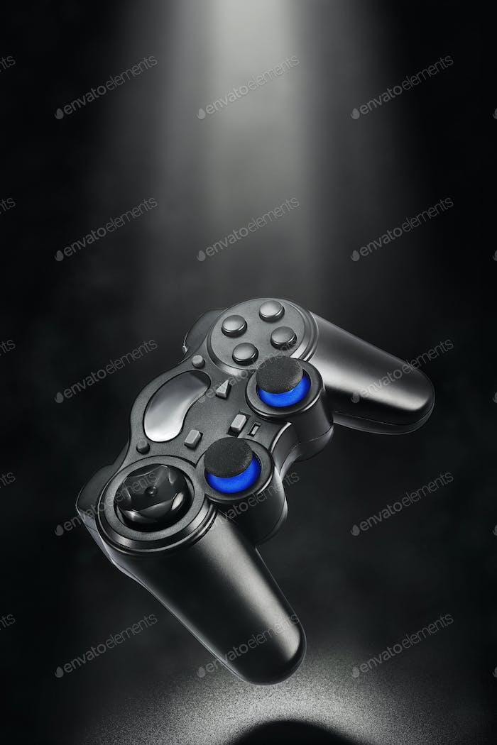 Black levitated wireless gamepad on dark background.