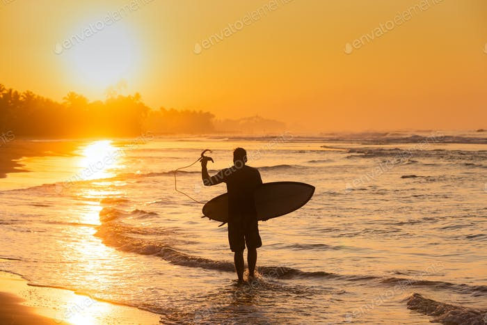 Silhouette of a surfer walking to the ocean during sunset