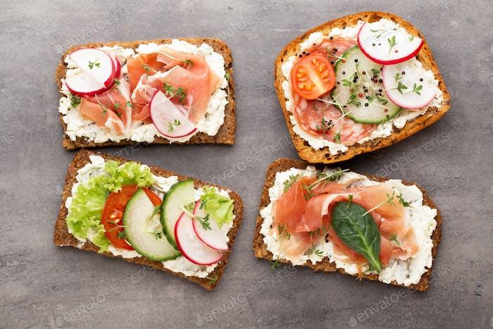 Sandwich mit Müsli Brot und Salami auf dunklem Marmorhintergrund.