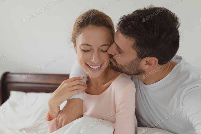 Front view of romantic Caucasian man kissing woman on bed in bedroom at comfortable home