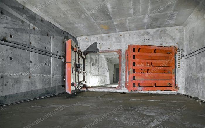 Concrete room underground with a ladder to the surface from which the light comes