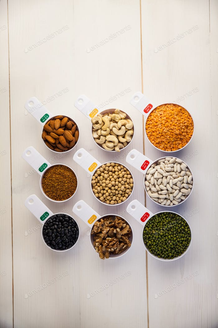 Portion cups of pulses seeds and nuts on wooden table