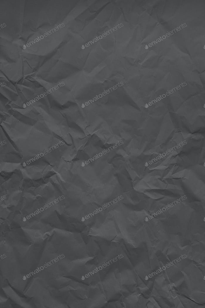Black crumpled wrinkled textured paper background. Empty space