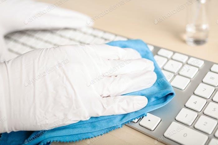 Hand mit Schutzhandschuh Reinigung einer Tastatur mit Desinfektionsmittel
