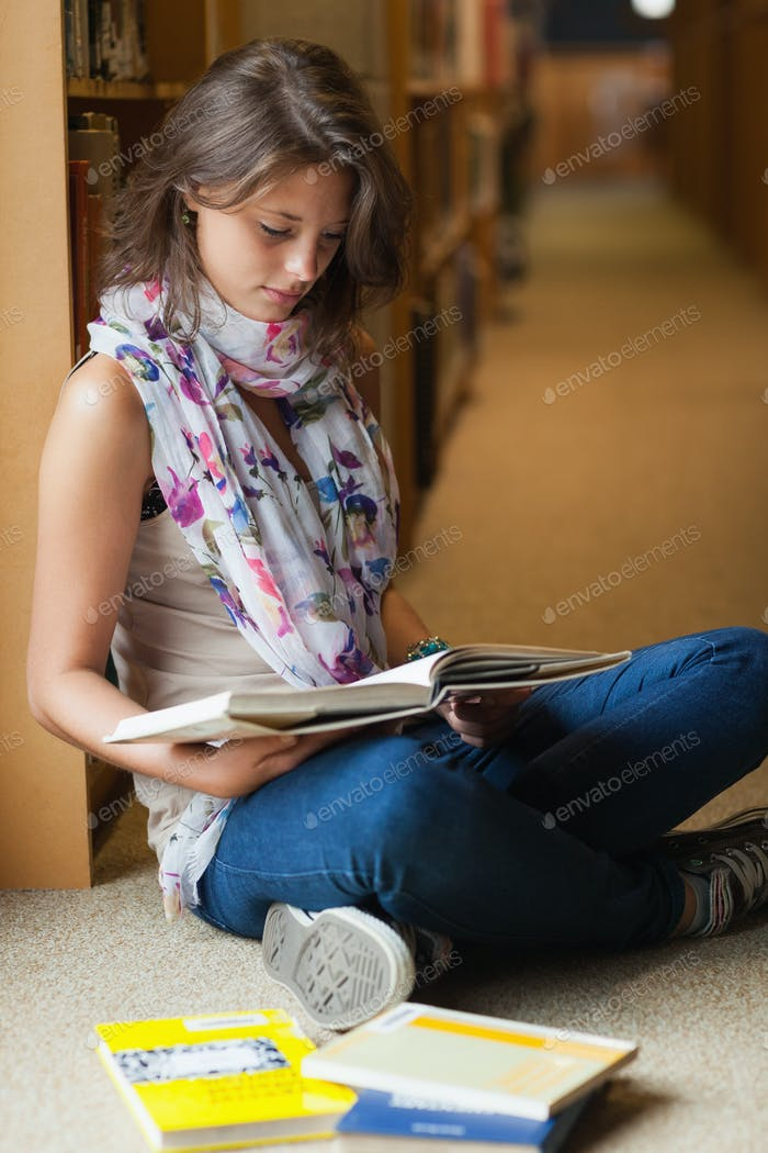 Full length of a female student sitting and reading a book in the library aisle