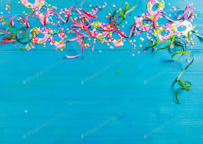 Carnival confetti and serpentines on blue background, top niew