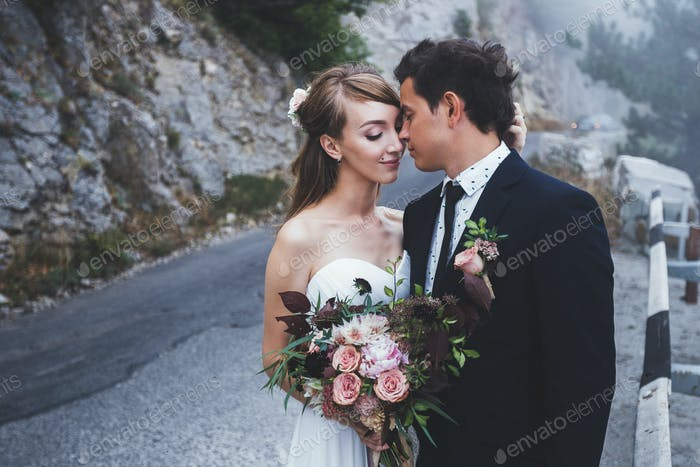Sensual portrait of wedding couple in mist weather. Photo in mountains