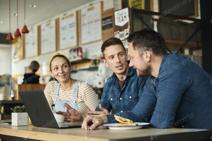Two men and a woman meeting in a cafe, looking at a laptop