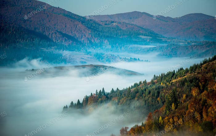 Beautiful morning landscape with autumn foggy mountains