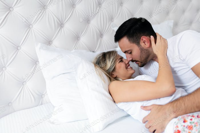 Happy couple having romantic times in bedroom