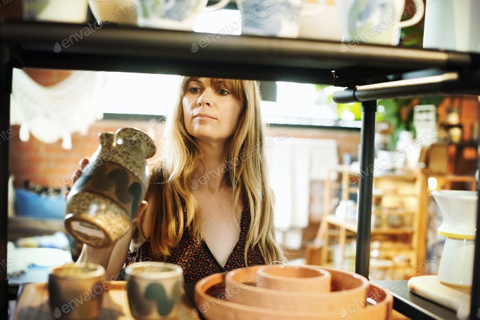 Woman standing in a shop, holding a small ceramic vase.