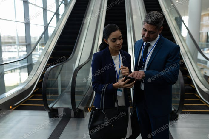 Businessman and businesswoman discussing over mobile phone near escalator in office