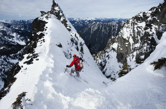 A skier ski-ing down a snow slope, powder skiing in the mountains in winter