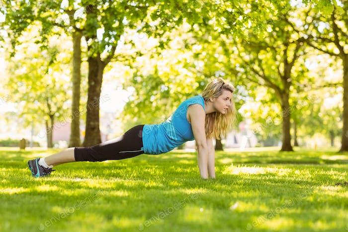 fit blonde tun Push-ups in den Park an einem sonnigen Tag