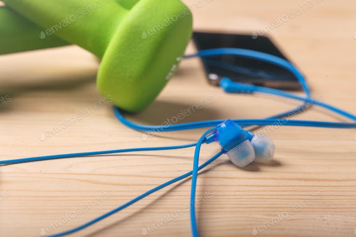 earphones on wooden table with blurred dumbbells and smartphone