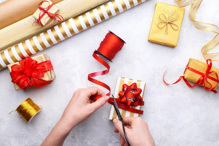 Woman's hands tying up Christmas or birthday gift box
