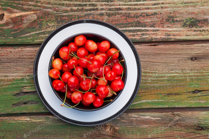 Fresh cherry in a plate on an old wooden background