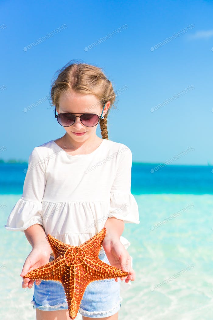 Adorable little girl with starfish on white empty beach