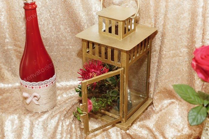 stylish decorated golden bottles of wine with red flowers