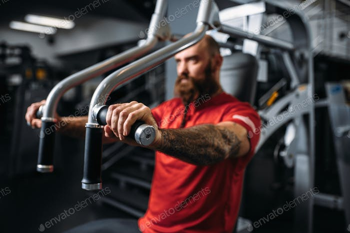 Muscular athlete on exercise machine in gym