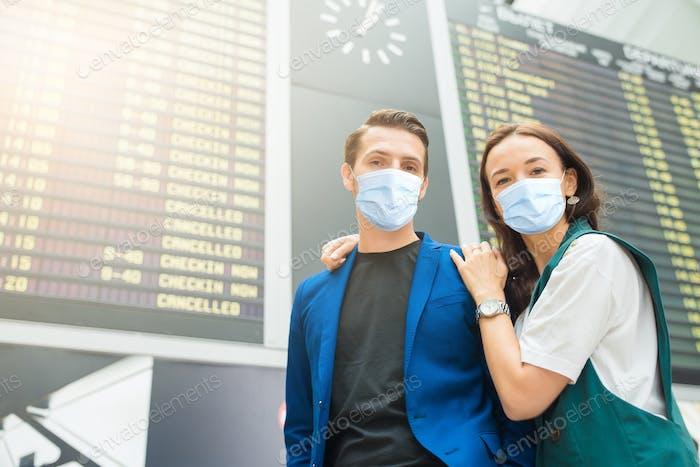 Junges Paar am internationalen Flughafen mit Blick auf die Fluginformationstafel