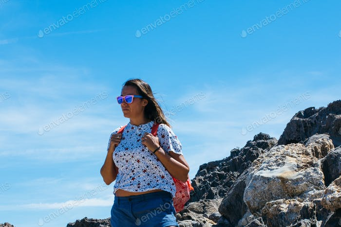 Woman with backpack on rock