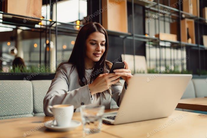 Mujer en la cafetería usando el teléfono móvil