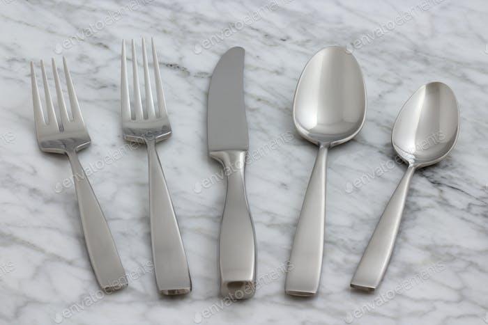 beautiful silverware on carrara marble