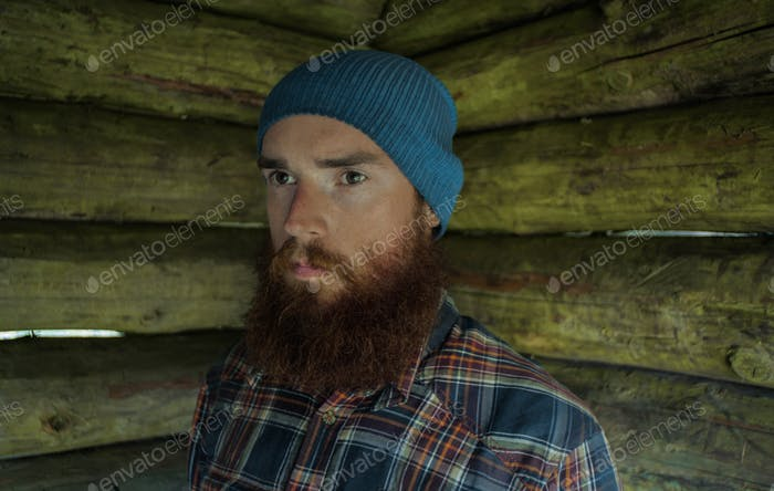 portarit of a ginger caucasian man with beard, wearing a hat and plaid shirt