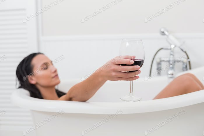 Pretty brunette taking a bath with glass of wine in a bathroom