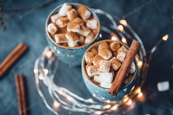 Hot chocolate with marshmallow and cinnamon in blue ceramic cups on a table