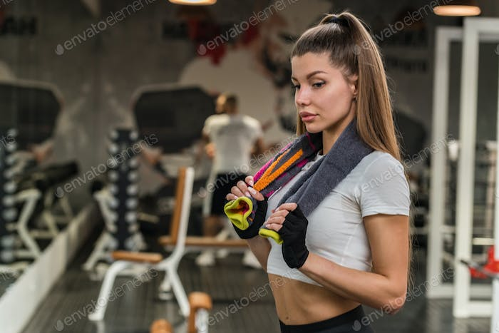 Portrait of young attractive fitness girl with towel in gym