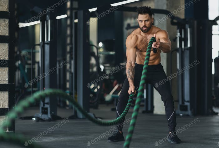 Athletic young man with battle rope doing exercise