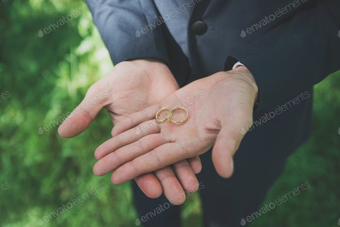 Two golden wedding rings on groom's palms. Wedding rings on the